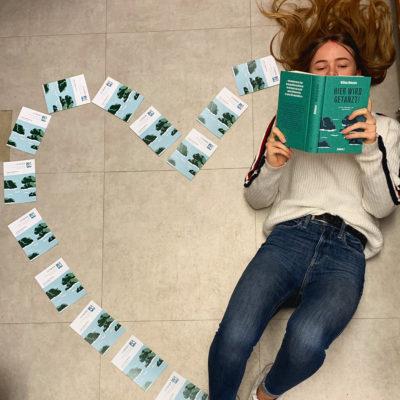 Ein auf dem Boden liegendes, lesendes Mädchen. Darum sind Prospekte so drapiert, das sie, zusammen mit dem Mädchen die Form eines Herzens bilden.